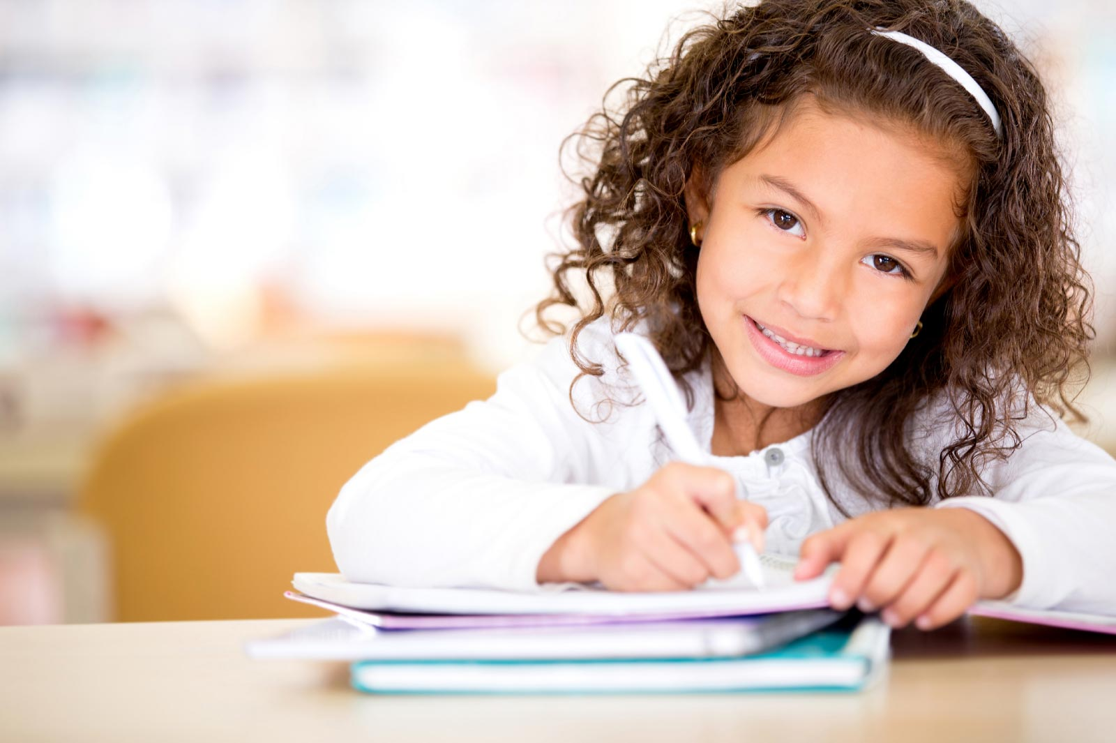 Little girl writing in a notebook.