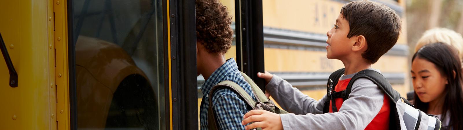Children get onto a school bus